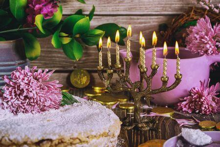 Jüdische Menora mit brennenden Kerzen und mit Blumen geschmückten Feiertagskuchen. Standard-Bild