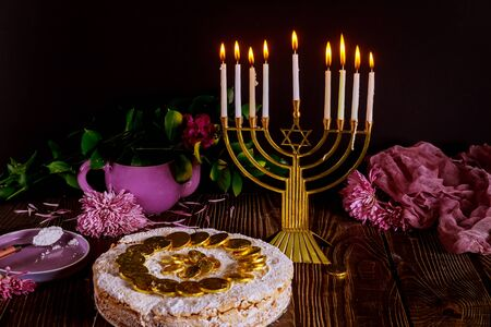 Hanukkah cake with chocolate coins on the top and menorah. Jewish holiday.