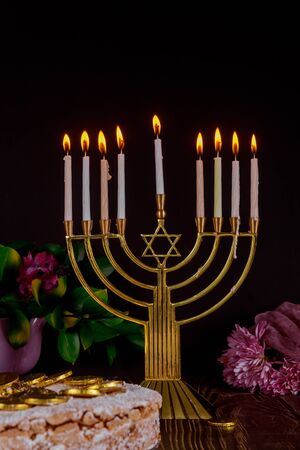Festive menorah with white burning candles and cake with chocolate coins on the top. Jewish holiday concept.