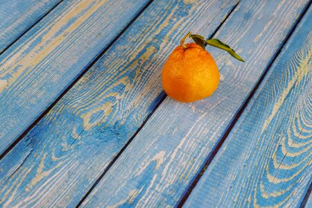 One tangerine with green leaf on wooden table.