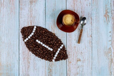 American football ball made from coffee beans with cup of fresh coffee and teaspoon.