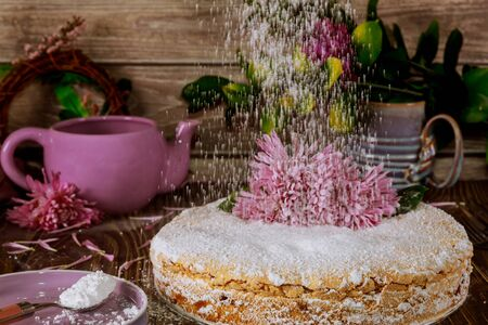 Powdered sugar sprinkles on cake with fresh flower with teapot on the table.