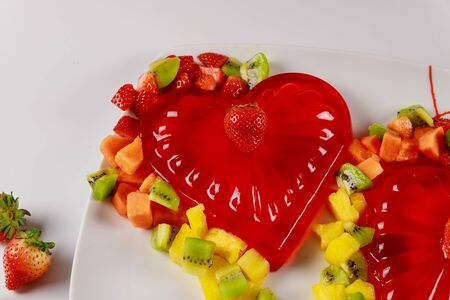 Strawberry gelatin hearts with fresh strawberries and pineapple. Valentines Day concept. Imagens