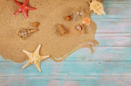 Ferienkonzepthintergrund mit Sand, Muscheln und Seesternen auf blauem Holz. Papyrus aus der Glasflasche mit Kork.