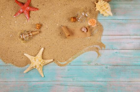 Vacation concept background with sand, shells and starfish on blue wood. Papyrus from the glass bottle with cork.