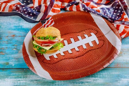 Sandwich on american football ball plate with american flag on wooden background. Foto de archivo - 137865819