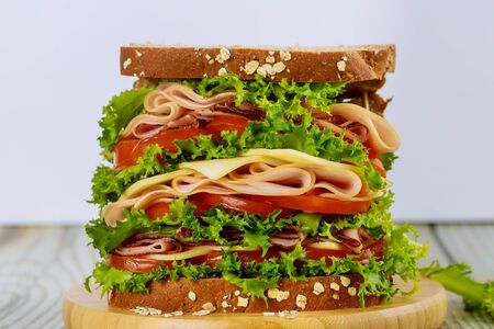 Delicious sandwich with ham and vegetables on wooden table. Foto de archivo - 137787193