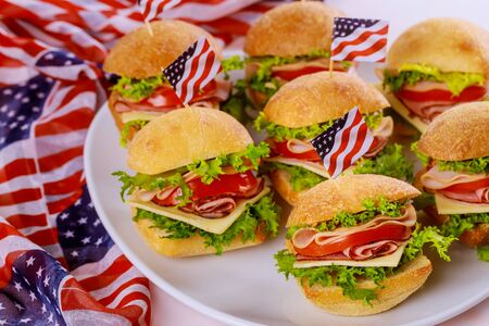 Tasty sandwiches with ham, tomato, cheese and lettuce with USA flag for american holiday. Foto de archivo - 137791334