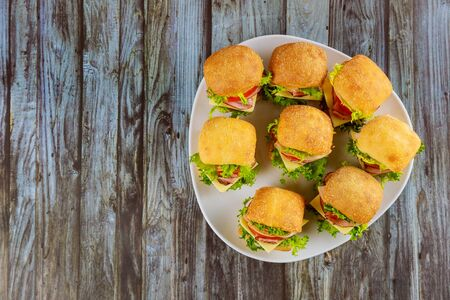 Small sandwiches with ham and vegetables on plate on wooden table. Foto de archivo - 137865834
