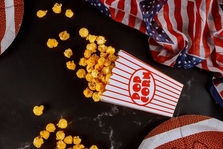 Caramel popcorn in striped box for watching american football game on tv. Sport concept. Zdjęcie Seryjne