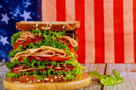Big sandwiche with ham, cheese and tomato for american holiday party table. Foto de archivo - 137865835