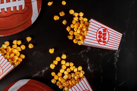 Yellow popcorn in striped boxes spilled on black background with american football plate. Watching sport game concept.