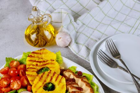 Healty exotic salad with grilled pineapple and olive oil in glass bottle.