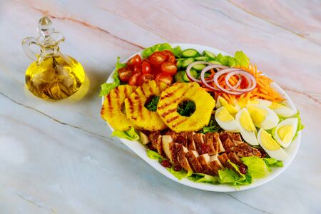 Exotic colorful salad with vegetable, chicken breast and grilled pineapple with olive oil in glass bottle. 版權商用圖片