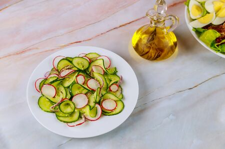 Vegetable salad from cucumber and radish with olive oil in glass bottle.