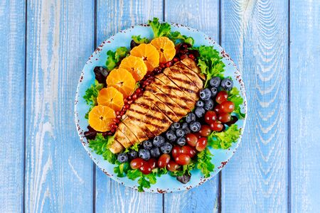 Salad with grilled chicken and vegetables on blue wooden table.