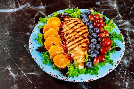 Colorful healthy salad with grilled chicken breast, vegetables and fruits.