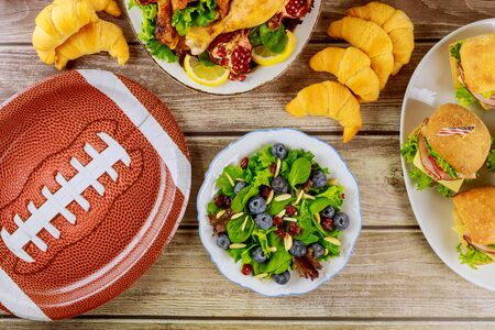 Party table with variety food for sport fans for watching american football game.