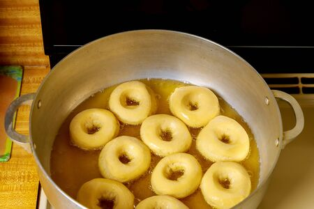 Frying round donuts with hole in hot oil. Banque d'images