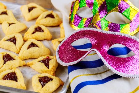 Hamantaschen jewish cookies on baking tray with tallit and mask for Purim.