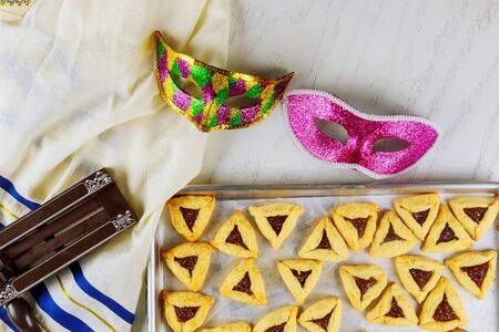 Jewish cookies Haman ears with jam for Purim with mask, tallit and noisemaker. Stock Photo