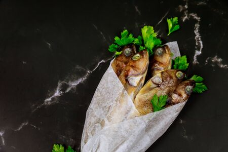 Raw whole fish with parsley wrapped in parchment paper on black table. Top view. Stock Photo