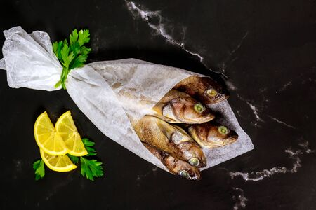 Healthy fresh raw fish on black board with lemon and parsley wrapped in parchment paper.. Seafood concept.