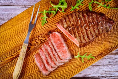 Grilled beef steak with arugula on cutting board with fork.
