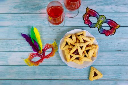 Jewish purim party table with wine, cookie and masks on background.