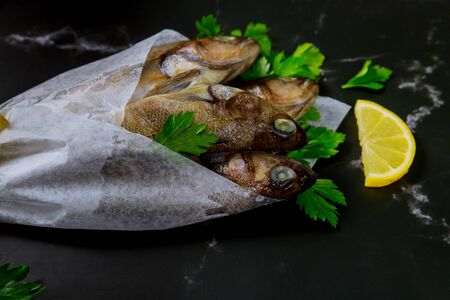 Healthy fresh raw fish on black board with ice. Seafood concept. Stock fotó