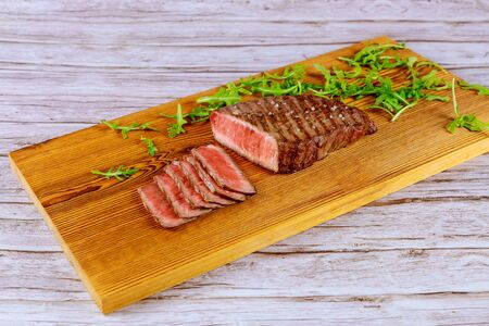 Grilled rare beef steak with arugula on cutting board.