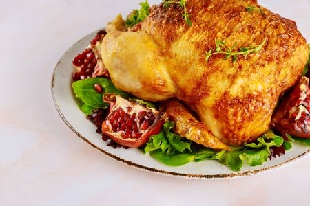 Whole roasted chicken on white plate with salad and pomegranate.