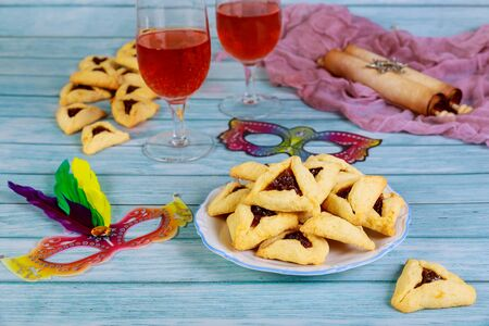 Jewish hamantashen cookies, mask, wine and megillah papyrus roll. Purim holiday background.