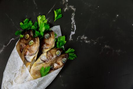 Uncooked whole fish with parsley wrapped in parchment paper on black table. Top view. Stock fotó