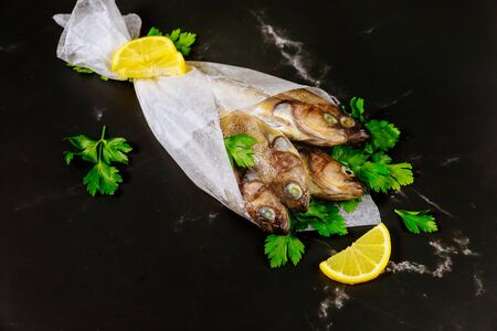 Raw whole fish with parsley and lemon wrapped in parchment paper on black table. Top view.