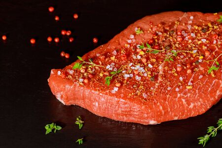 Raw sirloin beef steak with herb, salt and peppercorn over black stone board. Stock fotó