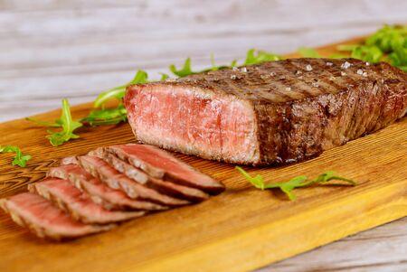 Sliced medium rare beef sirloin with arugula on wooden cut board.