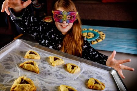 Jewish girl with long hair has fun and dancing in mask with cookies on Purim holiday.