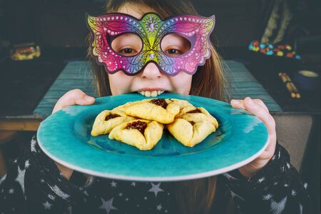 Jewish girl in carnival mask bites plate with purim hamantaschen cookies.
