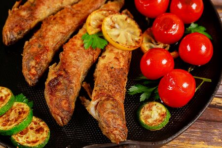 Delicious fried fish served with vegetables on black skillet on wooden table. Close up.
