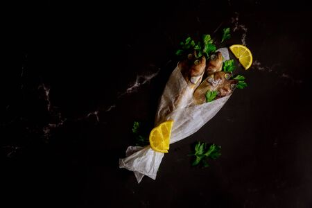 Whole fresh fish wrapped in parchment paper on black background. Top view.