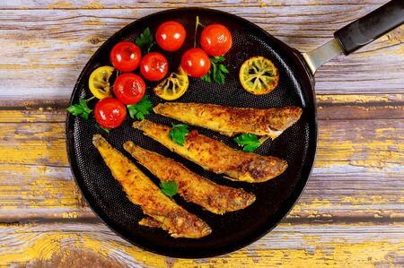 Tasty fish fried with vegetables and lemon on black skillet. Seafood concept.