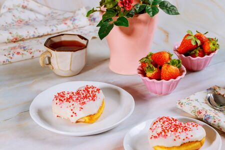 Party table with heart shaped donuts, strawberry, tea and vase with rose. Valentine Day concept.