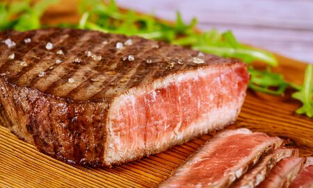 Grilled sliced rare angus beef steak with sea salt on wooden board. Close up.