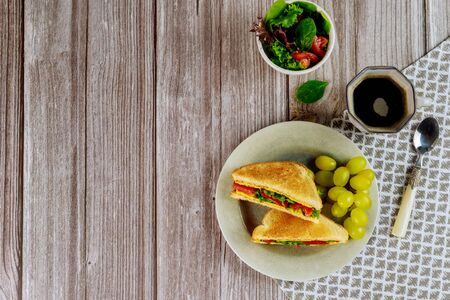 Healty grilled cheese sandwich with golden grape and cup of coffee for breakfast. Top view.
