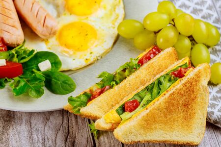 Healty and fitness breakfast with egg, salad, grape and grilled cheese toast.