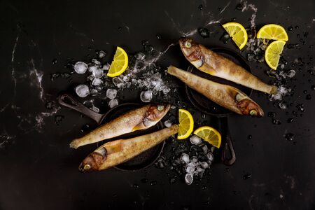 Raw whole fish with ice and lemon on black table. Top view. Stock fotó