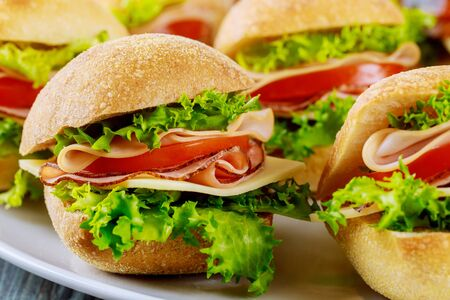 Delicious sandwiches made from ciabatta roll with ham, cheese, lettuce and tomato. Close up.