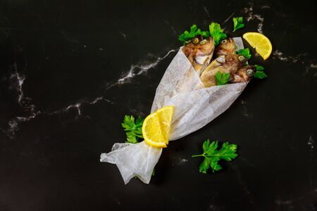 Fresh whole fish with parsley and lemon wrapped in parchment paper on black table. Top view. Stock fotó