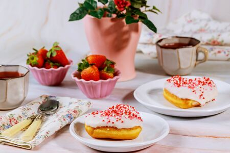 Tea party table with heart shaped donuts, strawberry and vase with red rose. Stock fotó